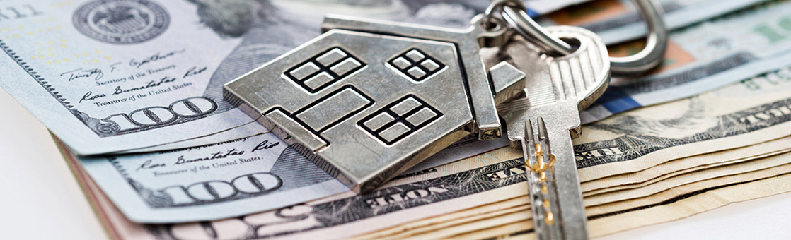 keys with house key chain on stack of money